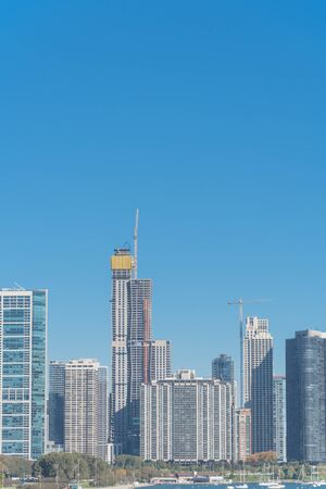 View to Chicago downtown from Lake Michigan with building density. Row of new and under construction skyline with working crane, yacht boats on foreground water Standard-Bild - 129318819