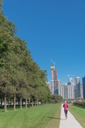 Rear view of fitness lady running at downtown park in Chicago along Michigan Lake. Healthy woman in fall sportswear exercise at daytime Stock Photo