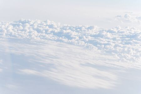 Beautiful and unusual Altocumulus or Cirrocumulus cloud formation seen from airplane window at sunrise. Skyline view above the clouds from the air Standard-Bild - 129318828
