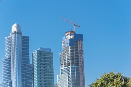 Close-up view buildings of Chicago downtown under clear blue sky. New and under construction skylines with working crane. Modern urban city skyscrapers background Standard-Bild - 129318832