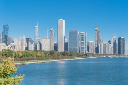 Lakefront Chicago skylines with trees from the park of Northerly Island along the shore of Lake Michigan Standard-Bild - 129318713