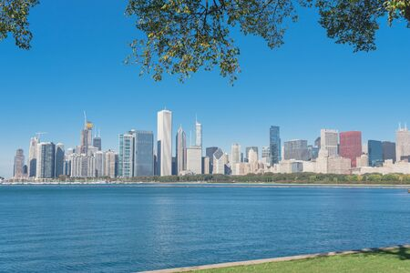 Lakefront Chicago skylines with trees from the park of Northerly Island along the shore of Lake Michigan Standard-Bild - 129318709