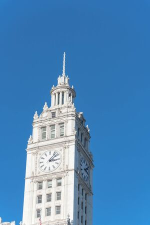 Low angle view top of traditional building with a clock faces pointing in all directions. Clock tower along Michigan Avenue in downtown Chicago, Illinois. Standard-Bild - 129318728