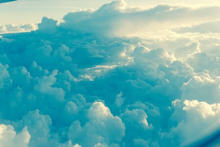 Vintage tone beautiful and unusual Altocumulus or Cirrocumulus cloud formation seen from airplane window at sunrise. Skyline view above the clouds from the air Standard-Bild - 129318732