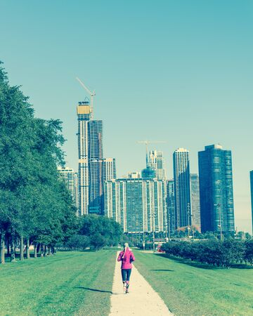 Vintage tone rear view of fitness lady running at downtown park in Chicago along Michigan Lake. Healthy woman in fall sportswear exercise at daytime Standard-Bild - 129318785