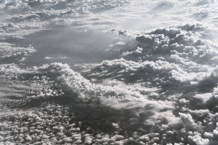 Vintage tone beautiful and unusual Altocumulus or Cirrocumulus cloud formation seen from airplane window at sunrise. Skyline view above the clouds from the air Standard-Bild - 129318788