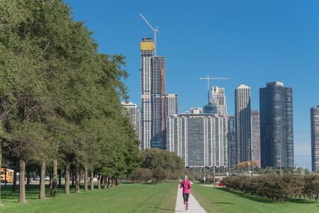 Rear view of fitness lady running at downtown park in Chicago along Michigan Lake. Healthy woman in fall sportswear exercise at daytime Standard-Bild - 129318666