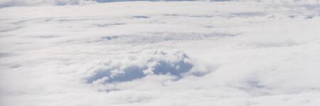 Panorama beautiful and unusual Altocumulus or Cirrocumulus cloud formation seen from airplane window at sunrise. Skyline view above the clouds from the air Standard-Bild - 129318684