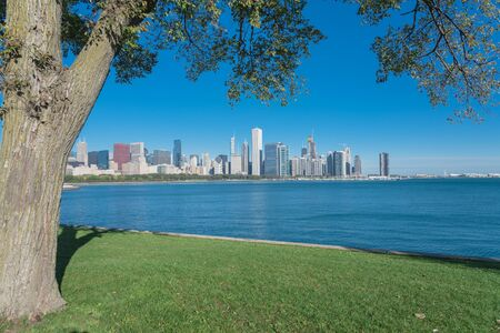 Lakefront Chicago skylines with trees from the park of Northerly Island along the shore of Lake Michigan Standard-Bild - 129318584
