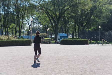 Fitness lady with fall sportswear and headphone running in Chicago park Standard-Bild - 129318594
