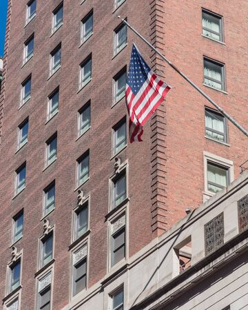 Proudly display of American flag outside of government building near Union Station in downtown Chicago, Illinois. Flying stars and stripes flag with historical brick building facade background Standard-Bild - 129318356