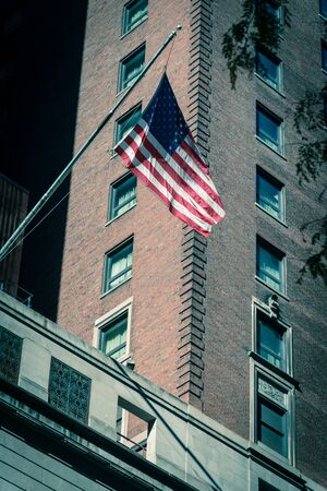 Vintage tone proudly display of American flag outside of government building near Union Station in downtown Chicago, Illinois. Flying stars and stripes flag with historical brick building facade Standard-Bild - 129318358
