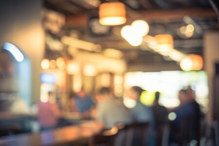 Abstract sfocata clienti maschi seduti sul bancone del bar presso il locale birrificio locale nel Kent, Washington. Sfondo sfocato stile di vita moderno nell'area urbana americana.