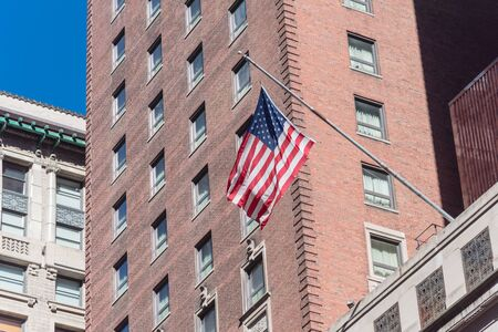 Proudly display of American flag outside of government building near Union Station in downtown Chicago, Illinois. Flying stars and stripes flag with historical brick building facade background Standard-Bild - 129318445