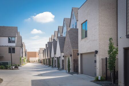 Large back alley of new development residential community with metal fence gate and well trim landscape outside of downtown Dallas, Texas. Row of two car garages from modern three story houses