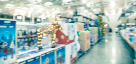 Blurred image LED lighted deer, pop up led  and huge Christmas trees decoration in wholesale store. Wreaths and strings of bokeh lights surround the artificial Christmas tree. Customer shopping 写真素材