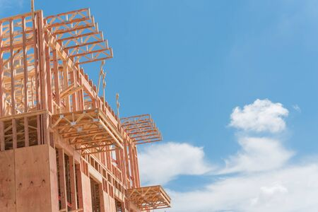 Low angle view of modern condominium building with large patio under construction near North Dallas, Texas, America. Wooden house with timber framing, truss, joist, beam close-up under cloud blue sky
