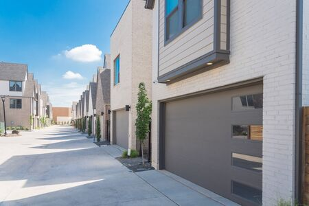 Row of garages from modern three story houses in North Dallas, Texas. Large back alley of new development residential community with metal fence gate and well trim landscape Stockfoto - 131435132