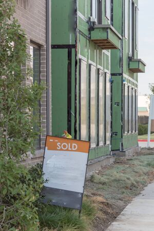 Front porch of modern house with Sold lawn sign near downtown Dallas, Texas. Brand new development urban house