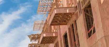 Panorama view low angle view of modern condominium building with large patio under construction near North Dallas, Texas. Wooden house with timber framing, truss, joist, beam close-up cloud blue sky