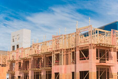 Multistory condominium under construction with wooden lumber timber framework and concrete elevator shaft. Modern apartment complex rental living space near Dallas, Texas Banco de Imagens