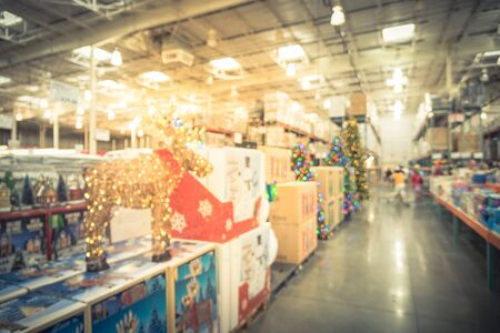 Blurred image LED lighted deer, pop up led snowman and huge Christmas trees decoration in wholesale store. Wreaths and strings of bokeh lights surround the artificial Christmas tree. Customer shopping Standard-Bild - 131435639