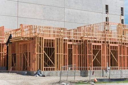 Close-up construction site of wooden urban apartment building with beam truss, metal fencing, large slab foundation near Dallas, Texas, America. Concrete wall of multilevel parking garage in background