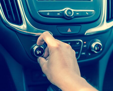Left hand turning knob on modern car cooling temp adjust to 64 Fahrenheit F degree. Asian male hand on dashboard air conditioner car interior Stok Fotoğraf