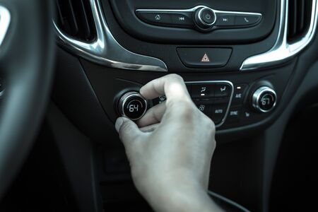 Filtered tone Asian left male hand turning knob button temperature adjust air conditioner to 64 F degree Stok Fotoğraf
