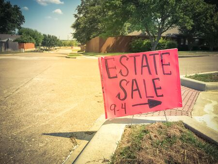 Close-up red estate sale sign with 9AM to 4PM timeframe at suburban neighborhood near Dallas