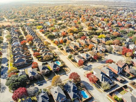 Lakeside residential neighborhood North of Dallas with new two story single family houses and colorful fall foliage. Bright orange color along local street and drive way, beautiful Texas autumn scene