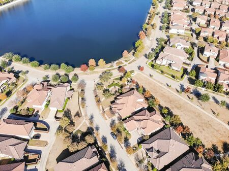 Top view new lakeside development subdivision near Dallas, Texas in a sunny fall day with colorful fall leaves. Row of single-family detached homes with wooden fence backyard and well trim landscape