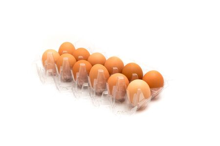 Close-up an open plastic box of a dozen fresh cage free grade A large brown eggs isolated on white background. Top view dozen eggs in cardboard container, paper egg box with clipping path, copy space.