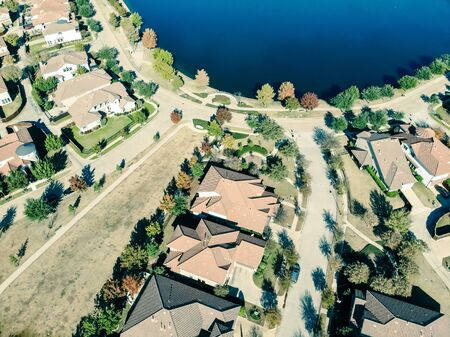 Vintage top view new lakeside development subdivision near Dallas in a sunny fall day with colorful fall leaves. Row of single-family detached homes with wooden fence backyard and well trim landscape