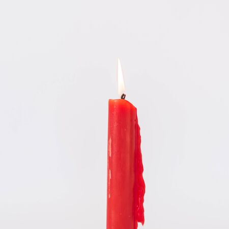 Close-up single red burning candle isolated on white background. Popular Asian stick candle for daily and holiday uses.
