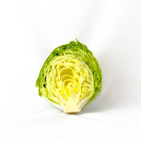 Close-up view of a half cut fresh green iceberg lettuce saladisolated on white background.Organic food background with copyspace.
