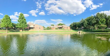Panorama view waterfront house with row of mature bold cypress trees in suburbs Dallas, Texas, USA. Suburban single family detached home along river with high stone retaining wall, green grass lawn