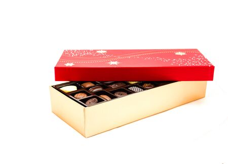 Partly open chocolate box with variety of truffle isolated on white background. Festive chocolate confectionery for holidays and special events