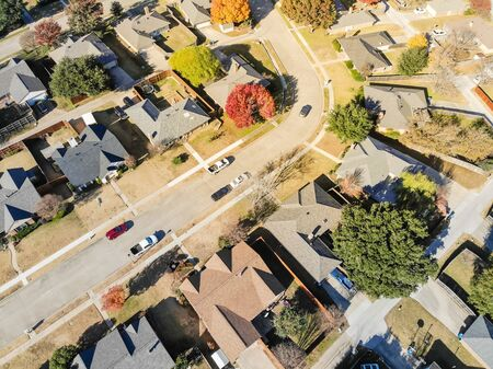 Looking down view of residential neighborhood in sunny autumn day with colorful fall foliage. Top of new development subdivision with row of single family house, and cars commuting on local street