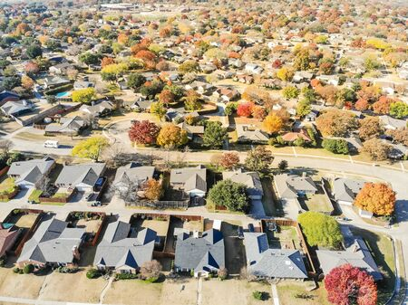 New development neighborhood near Dallas, Texas with colorful orange autumn leaves. Row of two story single family dwelling with large backyard, swimming pool, attached garage and wooden fence garden