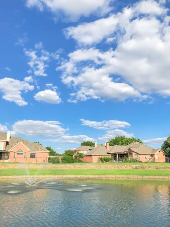 Lakefront houses with water fountain and green grass lawn bank in suburbs Dallas, Texas, USA. Suburban single family detached home along river with high stone retaining wall, sewage, mature tree