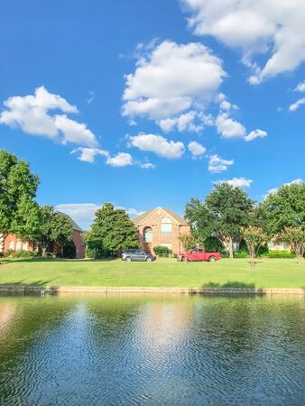 Riverside residential neighborhood in suburbs Dallas, Texas, USA. Row of single family detached homes with parked car on street, mature oak trees, high stone retaining wall, green grass lawn, blue sky