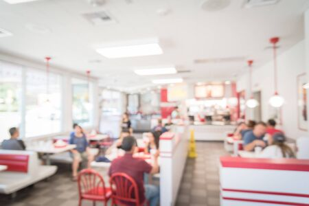Blurred image a compact fast food restaurant in Austin, Texas, USA. People serving sauce, ketchup and enjoying lunch with burgers, fried fries and sugar drink. Natural light with bokeh abstract.