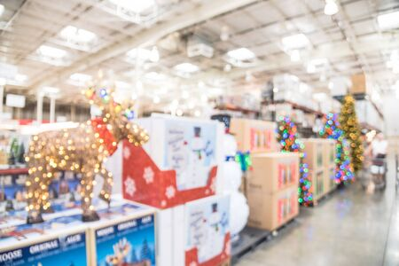 Blurred image LED lighted deer, pop up led snowman and huge Christmas trees decoration in wholesale store. Wreaths and strings of bokeh lights surround the artificial Christmas tree. Customer shopping