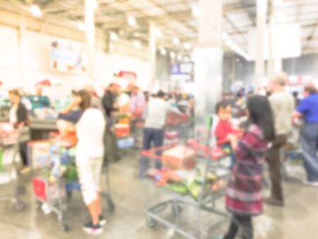 Blurred image cashier with long line of people at check-out counter of wholesale store in America. Customers paying with credit card to store clerks, full cart of groceries. Cashier register concept