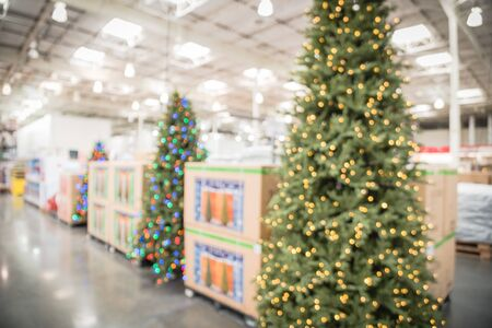 Blurred image huge Christmas trees decoration in wholesale store. Wreaths and strings of bokeh lights surround the artificial Christmas tree. Xmas decorations cheerful displayed for selling in America