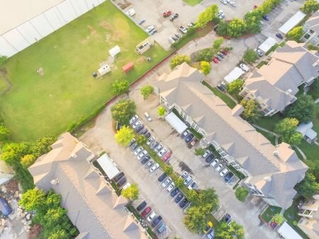 Aerial view apartment building complex near large industrial and warehouse building in Houston, Texas, USA. Top of rental units with swimming pool and outdoor parking lots