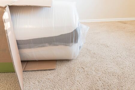 Top view brand new roll-packed spring mattresses on carpet floor of apartment bedroom in Texas, America. Foam and latex hybrid material mattress being unboxed from cardboard box