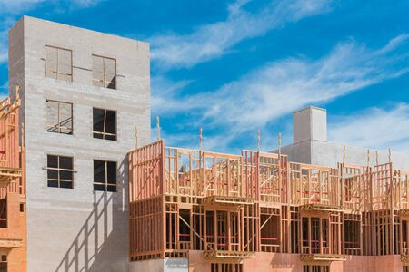 Modern condominium building under construction with wooden lumber timber framework and concrete elevator shaft. Luxury apartment complex with multilevel garage near Dallas, Texas
