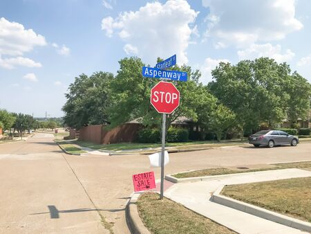 All way stop and estate sale sign at suburban neighborhood near Dallas, Texas, America. Lawn sale sign on the sidewalk near local drive intersection